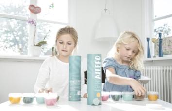 ailefo paprør står på bordet mellem to piger, der leger med leger med ailefo økologisk modellervoks, europas første og eneste økologiske modellervoks