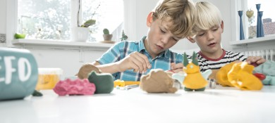 two concentrated boys playing with ailefo organic modeling clay